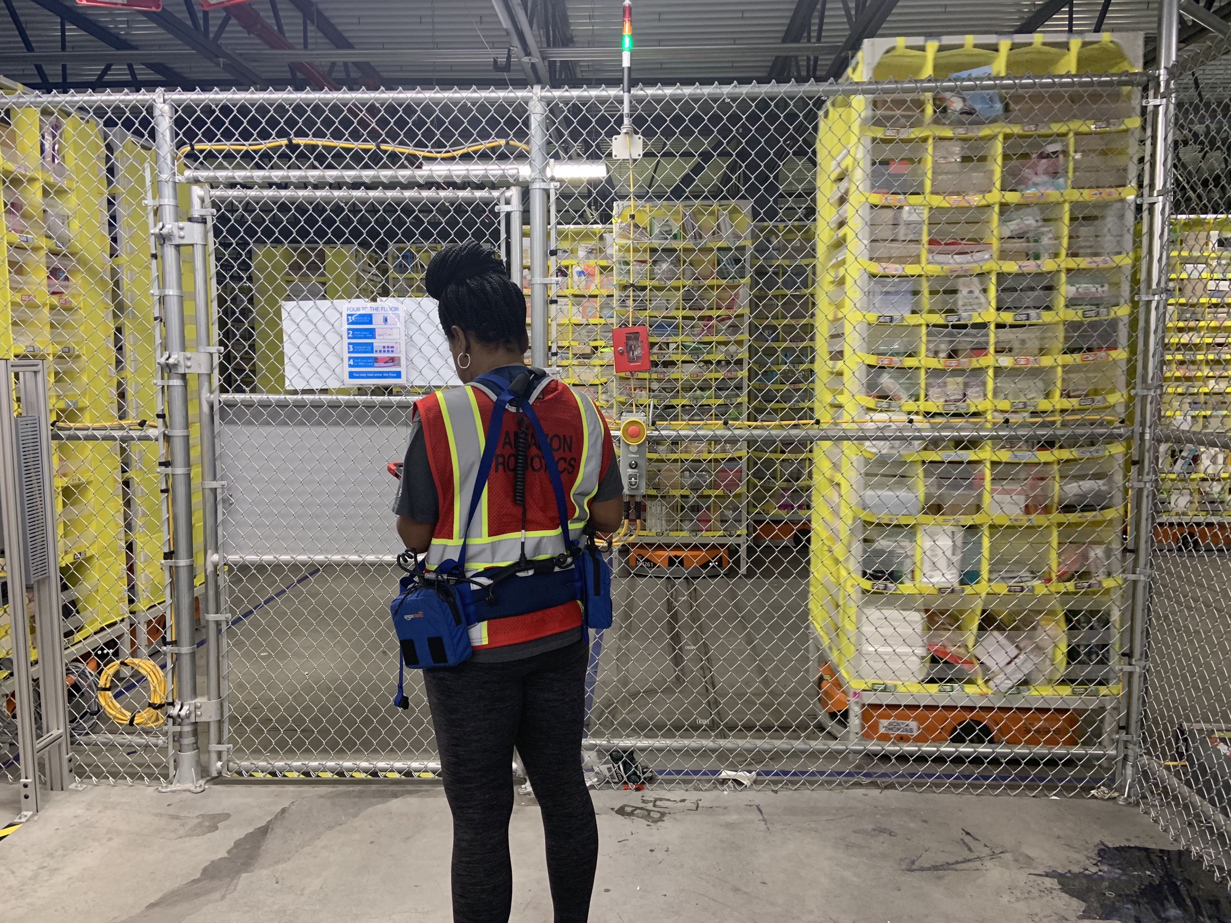 "An Amazon Robotics tech consults her tablet outside the cage where robotic ""drives"" ferry merhcandise around a Staten Island, New York, fulfillment center."